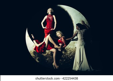 Beautiful young women with fashionable hair posing on crescent moon in long evening elegant dress red and white color on black background