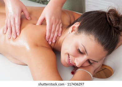 Beautiful young women getting a massage in massage salon.