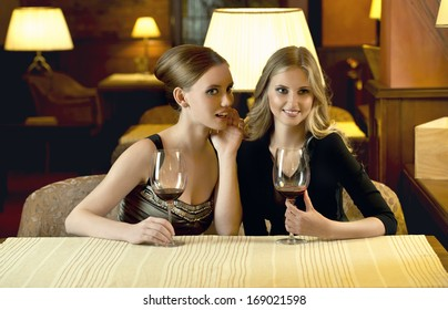 Beautiful young women with glass of red wine in restaurant