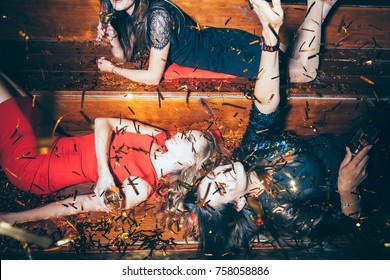 Beautiful young women having fun on crazy party lying on the floor in confetti. New year, Birthday, Holiday Event Concept