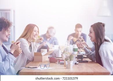 Beautiful young women having lunch break at an advert agency office