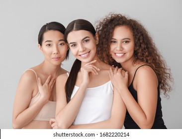 Beautiful young women with healthy skin on light background