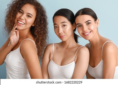 Beautiful young women with healthy skin on color background