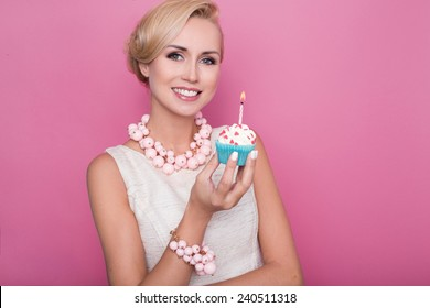 Beautiful young women holding small cake with colorful candle. Birthday, holiday. Studio portrait over pink background