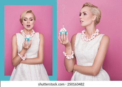 Beautiful young women holding small cake with colorful candle. Birthday, holiday. Studio portrait over pink and blue background