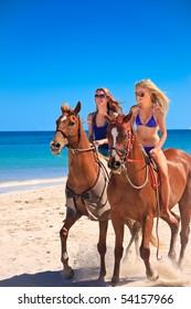 Beautiful young women horse riding on a tropical beach