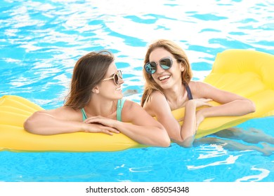 Beautiful young women with inflatable mattress relaxing in blue swimming pool