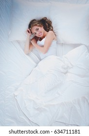 Beautiful young women lying on bed at home