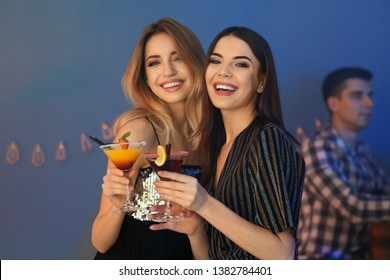 Beautiful young women with martini cocktails in bar