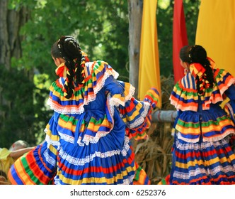 Beautiful young women perform a traditional dance in dresses of bright ribbons  and lace for a festival at an ancient hacienda in the southwestern United States.