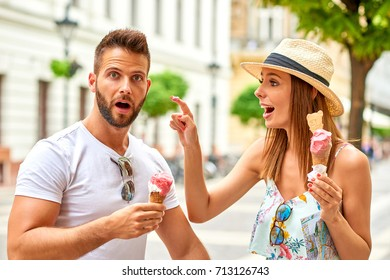 A beautiful young women is putting ice-cream with her finger on her boyfriendâ??s nose on the street of Budapest, Hungary.