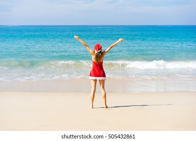Beautiful young women in red christmas clothes with raised up hands on sea beach. New year holidays in tropical countries concept.