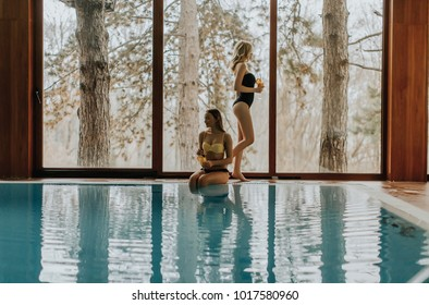 Beautiful young women relaxing by swimming pool in spa center and drinking juice