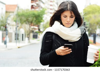 beautiful young women sending message with smartphone on the street.