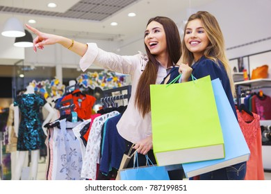 Beautiful young women with shopping bags pointing at something in shopping store.