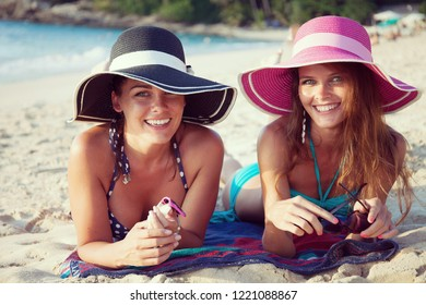 Beautiful young women in sunhats laying on beach