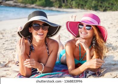 Beautiful young women in sunhats laying on beach