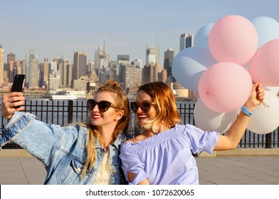 Beautiful young women taking a selfie with her smartphone on New York view. Fashionable girls with balloons, summer travel in USA