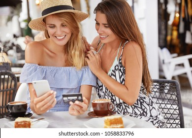 Beautiful young women tourists spend summer holidays abroad, book tickets online with smart phone and plastic card, spends leisure time, sit together in coffee shop, drink espresso or latte.