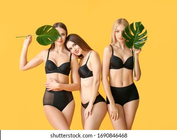 Beautiful young women in underwear and with tropical leaves on color background