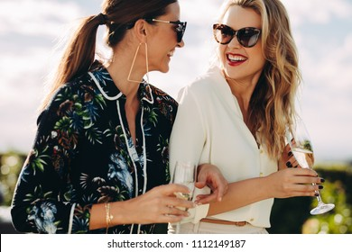 Beautiful young women walking together with glass of wine. Stylish female friends with wine walking outdoors.