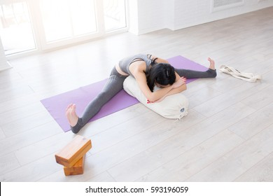 Beautiful young yoga girl lying in asana Shavasana or Corpse Pose using bolster. Fitness woman resting after working out, doing yoga exercise near a window on gym