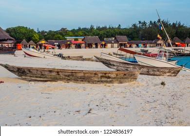 Beautiful Zanzibar coast line. Wooden fishing boat on sandy beach with blue water background, Zanzibar, Tanzania