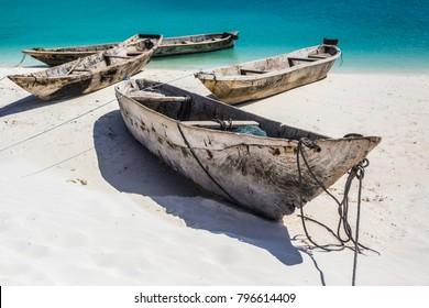 Beautiful Zanzibar coast line. Wooden fisherman boats on sandy beach with blue water background, Zanzibar, Tanzania