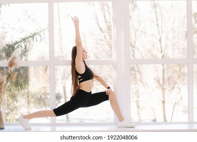 Beautifull brunette woman doing stretching on windowsill at home. Attractive fit girl training at home. Copy space