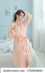 Beautifull brunette woman with long  hair in a pink linen nightgown