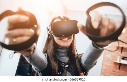 The beautifull girl playing games with virtual reality goggles at the office
