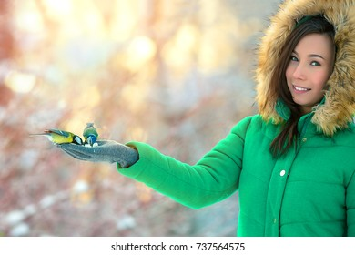 Beautifull girl pour seeds in bird feeder in winter snowy garden. Bluetit perched on a girls hand in a wintery scene.