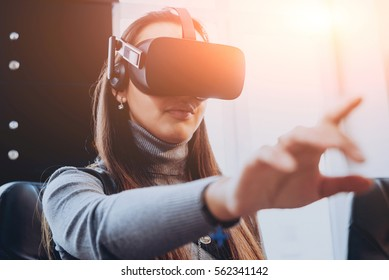 The beautifull girl wearing virtual reality goggles at the office