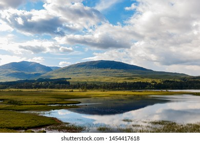 Beautifull lake reflecting in the water of Loch Tulla near Bridge of Orchy, Scotland, Cloudy sky with sun breaking through