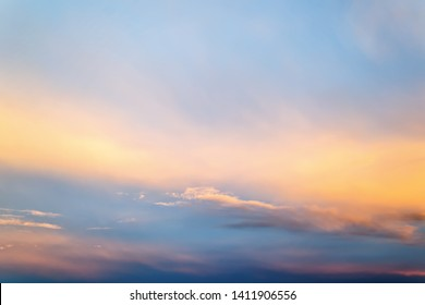 Beautifull skyscape at evening. Blue clear sunset sky with white and orange clouds. Calm background.