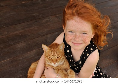 beautifull smiling red hair little girl sitting and holding a ginger cat. red hair model.  ginger girl. cute and pretty small girl in dress.