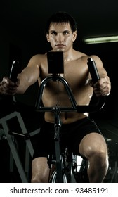 beautifull strong athletic guy,  execute exercise on exercise-bicycle, in  sport-hall