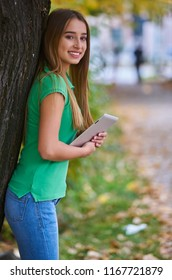 Beautifull young girl wearing in autumn colours using tablet