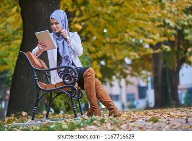 Beautifull young girl wearing hijab in autumn colours using tablet