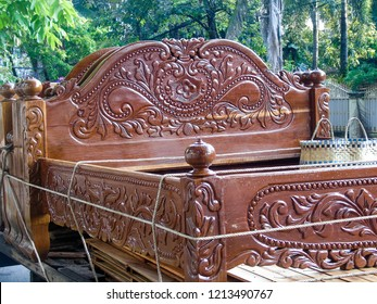 A beautifully carved bed is transported through the streets in Kampot, Cambodia