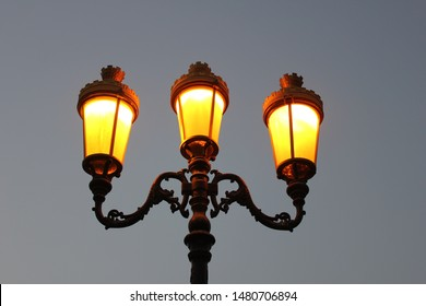 Beautifully carved Oriental street lights or street lamps cast a beautiful golden yellow glow at dusk time in a modern city. Electric street lights on poles were first used in 1878 in Paris city.