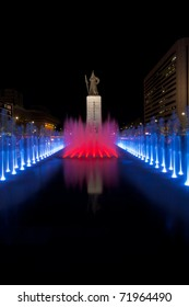 A beautifully colored red blue water fountain illuminates the front of the centered historic Admiral Yi Sun Sin statue at night in downtown Seoul, South Korea. Vertical copy space