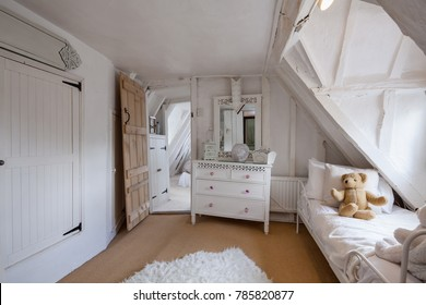 Beautifully decorated bedroom within 16th Century English cottage decorated in shades of white featuring sloping floors and misaligned doorways, chest of drawers, childs daybed with teddy bear.