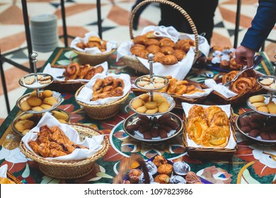 Beautifully decorated catering banquet table with variety of different pastry and bakery, with croissants and cookies on corporate christmas birthday party event or wedding celebration