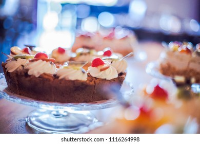 Beautifully decorated catering banquet table with different cakes as cottage cheese, apple and whipped cream on corporate christmas birthday party event or wedding celebration