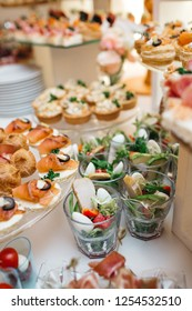 Beautifully decorated catering banquet table with profiteroles, salads and cold snacks. Variety of tasty delicious snacks on the table. Wedding table serving. Meat and vegetables