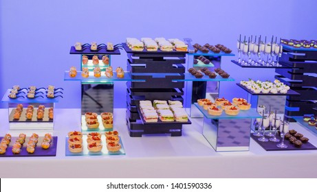 Beautifully decorated catering banquet table with different food snacks and appetizers. Banquet fourchette set with canapes close-up.