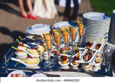 Beautifully decorated catering banquet table with different food snacks and appetizers with sandwich, caviar, fresh fruits on corporate christmas birthday kids party event or wedding celebration