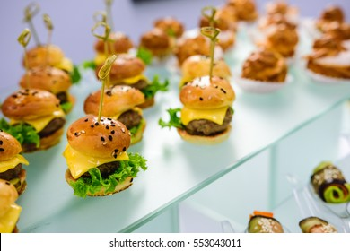 Beautifully decorated catering banquet table of mini cheeseburgers. Finger food on a glass tray