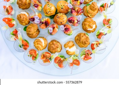 Beautifully decorated catering banquet table with burgers and profiteroles. Variety of tasty delicious snacks on the table
